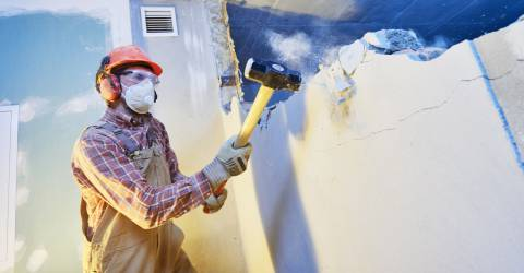 Man slaat met een hamer de binnenmuur van een huis kapot