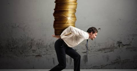 Zakenman draagt ??op zijn rug een stapel muntstukken